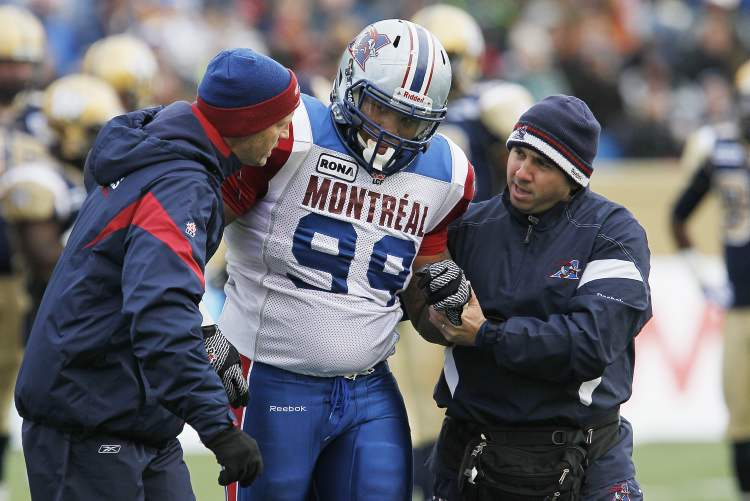 Montreal Alouettes' Scooter Berry (99) heads off the field with an injury during the first half of their CFL game against Winnipeg Blue Bombers in Winnipeg on Saturday.