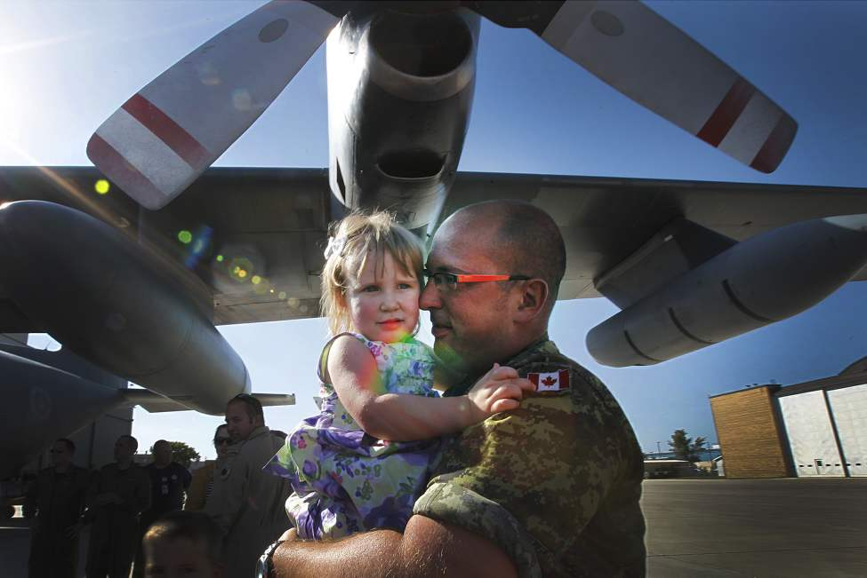 Two year old Mackenzie holds tight as her dad Master Corporal Ryan Maher holds her after he returned home at 17 Wing from the Libyan Operation Mobile which is based in Italy. September 9, 2011