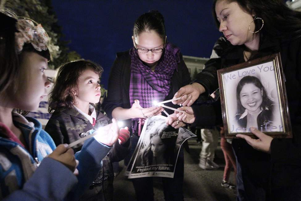 Elissa Gabriel (C) lights candles for Mary Catcheway (R), the sister of Jennifer Catcheway, and some children at a vigil for murdered and missing women in Winnipeg. October 8, 2011