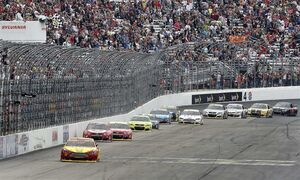 Joey Logano, front, gets the checkered flag to win the NASCAR Sprint Cup series auto race at New Hampshire Motor Speedway on Sunday, Sept. 21, 2014, in Loudon, N.H. (AP Photo/Jim Cole)