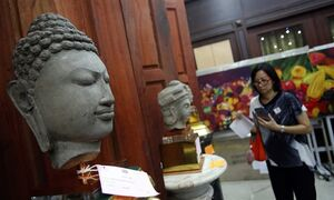 In this March 2, 2015 photo, a Thai visitor examines Buddha heads ahead of an auction of items seized from Lt. Gen. Pongpat Chayapam in Bangkok, Thailand. The four-day auction at a military base outside Bangkok opened Thursday, March 5 featuring what police say are the ill-gotten artworks and luxury goods seized from Pongpat, the longtime head of the Central Investigation Bureau, or Thailand's FBI. Pongpat is now in prison serving a 31-year-sentence on a range of corruption charges and insulting the monarchy. (AP Photo/Sakchai Lalit)