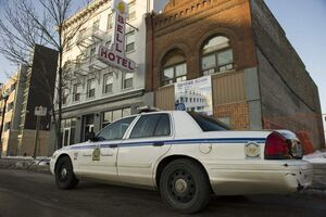 Police officers attend to the Bell Hotel Sunday morning. Two women and a man were stabbed late Saturday night in a suite in the hotel.
