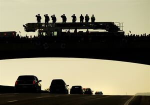 Supporters pay tribute as the Body of Cpl. Nathan Cirillo is transported in a hearse from Ottawa to Hamilton, along the Highway of Heroes in Porthope, Ont., on Friday, October 24, 2014. THE CANADIAN PRESS/Nathan Denette