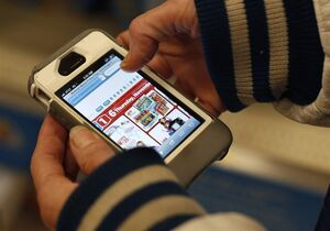 FILE - In this Nov. 28, 2014 file photo, a Target shopper uses her iPhone to compare prices at Wal-Mart while shopping after midnight in South Portland, Maine. Increasingly, buying products online is like trading stocks: you can buy a copper mug or a coat and then hours _ or even minutes later _ it can go up and down in price. (AP Photo/Robert F. Bukaty, File)