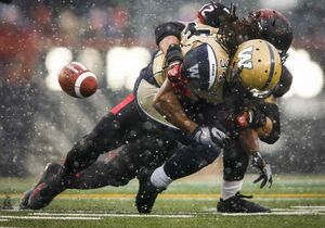 Winnipeg Blue Bombers' Paris Cotton, right, fumbles the ball as he is tackled by Calgary Stampeders' Juwan Simpson, during the first half of Saturday's game in Calgary.