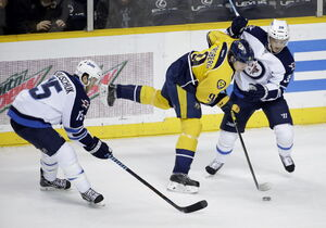 Nashville Predators center Filip Forsberg (9) moves the puck between Winnipeg Jets defenders Matt Halischuk (15) and Tobias Enstrom (39) in the first period of Saturday's game.