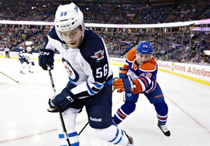 Winnipeg Jets Adam Lowry (56) and Edmonton Oilers Brad Hunt (59) battle in the corner during first period NHL hockey action in Edmonton Monday.