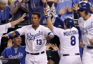 Kansas City Royals' Mike Moustakas (8) celebrates with Salvador Perez (13) and other players after hitting an inside-the-park home run in the eighth inning of a baseball game against the Cleveland Indians at Kauffman Stadium in Kansas City, Mo., Thursday, July 24, 2014. (AP Photo/Colin E. Braley)