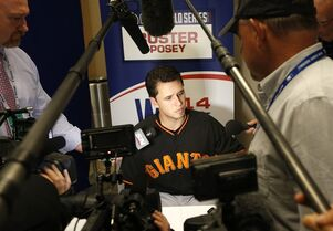 San Francisco Giants catcher Buster Posey talks to the media during baseball player availability at Kauffman Stadium in Kansas City, Mo., Monday, Oct. 20, 2014. The Kansas City Royals will host the San Francisco Giants in Game 1 of the World Series on Oct. 21. (AP Photo/Orlin Wagner)
