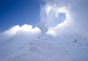 A cross lies on top of a church built entirely from ice blocks cut from a frozen lake before a religious blessing service at the Balea Lac resort in the Fagaras mountains, Romania, Thursday, Jan. 29, 2015. The blessing was performed jointly by priests from all Christian denominations in Romania and the church, built at an altitude of over 2,000 meters, will host all types of religious events like weddings and baptizing ceremonies as long as the cold weather lasts.(AP Photo/Vadim Ghirda)