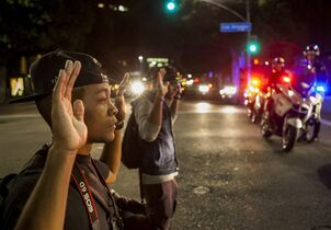 Protesters kneel down with their hands up in front of Los Angeles police officers in downtown Los Angeles on Wednesday, Nov. 26, 2014. People protesting the Ferguson, Mo., grand jury decision took to the streets in cities across the U.S. for a third day Wednesday. (AP Photo/Damian Dovarganes)