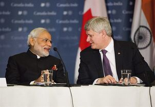 Canadian Prime Minister Stephen Harper, right, participates in a business roundtable with India's Prime Minister Narendra Modi, left, in Toronto on Thursday, April 16, 2015. THE CANADIAN PRESS/Michelle Siu