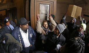 Protesters confront law enforcement officers as they try to enter City Hall Wednesday, Nov. 26, 2014, in St. Louis. Several people protesting the Ferguson grand jury decision stormed into City Hall in St. Louis on Wednesday, leading police to lock down the building and to call in more than a hundred additional officers. At least two people were arrested after the incident, in which the protesters shouted