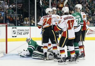 Dallas Stars goalie Kari Lehtonen of Finland looks back to see Calgary Flames' Jiri Hudler (24) of the Czech Republic celebrating his score with Johnny Gaudreau (13) and Sean Monahan (23) in the second period of an NHL hockey game Monday, March 30, 2015, in Dallas. (AP Photo/Tony Gutierrez)