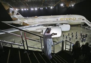 An Emirati man takes a selfie in front of a new Etihad Airways A380 in Abu Dhabi, United Arab Emirates, Thursday, Dec. 18, 2014. (AP Photo/Kamran Jebreili)