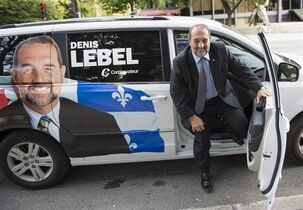 Tory MP Denis Lebel arrives in his marked van to address supporters Monday, August 25, 2014 in Montreal. A pre-electoral push by the federal Conservatives is underway in Quebec to charm Quebecers even though the next election could be more than a year away. Lebel is trying to woo a province where the party holds just five seats and polls have often suggested it sits fourth in popular support. THE CANADIAN PRESS/Paul Chiasson