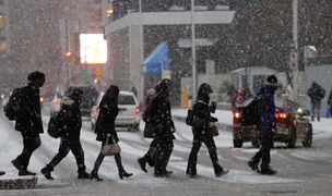 Pedestrians cross Graham Avenue as snow squalls track across the city.