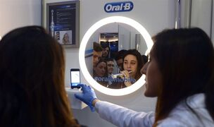 A woman uses an interactive electric toothbrush from Oral-B connected with a smartphone with bluetooth at the Mobile World Congress, the world's largest mobile phone trade show in Barcelona, Spain, Wednesday, March 4, 2015. (AP Photo/Manu Fernandez)