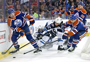 Winnipeg Jets' Chris Thorburn (22) battles for the puck with Edmonton Oilers' Justin Schultz (19), Boyd Gordon (27) and Nikita Nikitin (86) during first period NHL hockey action in Edmonton on Monday.