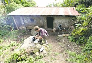 Chris Temple and Ryan Christofferson preparing food outside the dirt-floor hut where they lived for a summer in the village of Pena Blanca, Guatemala.