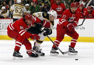 Boston Bruins' Carl Soderberg (34) charges between Carolina Hurricanes' Ron Hainsey (65) and Justin Faulk (27) during the first period of an NHL hockey game, Sunday, March 29, 2015, in Raleigh, N.C. (AP Photo/Karl B DeBlaker)