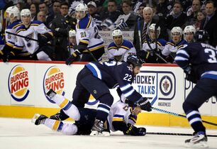 Winnipeg Jets' Chris THorburn takes down St Louis Blues' Jaden Schwartz in front of the Blues bench in the first period of Thursday's game at the MTS Centre.