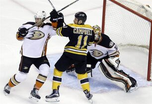 Anaheim Ducks defenseman Cam Fowler, left, and Boston Bruins center Gregory Campbell (11) battle for position as Ducks goalie Frederik Andersen (31) guards the net in the first period of an NHL hockey game in Boston, Thursday, March 26, 2015. (AP Photo/Elise Amendola)