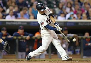 Minnesota Twins' Kurt Suzuki hits an RBI double off Detroit Tigers pitcher David Price in the first inning of a baseball game, Wednesday, Sept. 17, 2014, in Minneapolis. (AP Photo/Jim Mone)