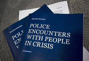 Copies of former Supreme Court of Canada justice Frank Iacobucci's report on the investigation into the use of lethal force by Toronto police are pictured at a press conference at Toronto Police headquarters in Toronto on Thursday, July 24, 2014. THE CANADIAN PRESS/Darren Calabrese