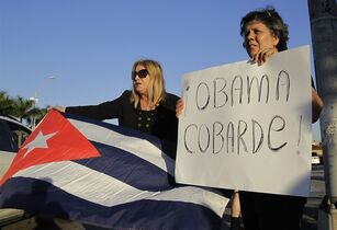 Ana Lourdes Cuesta, left, and Liliana Cuerra, of Miami, protest in Miami, Wednesday, Dec. 17, 2014, the Obama administration's decision to re-establish diplomatic relationships with Cuba. Cuerra holds a sign that reads