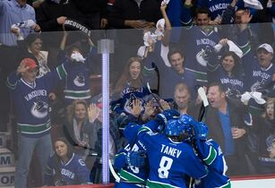 Vancouver Canucks' Nick Bonino is mobbed by his teammates after scoring against the Calgary Flames during the second period of game 5 of an NHL Western Conference first round playoff hockey series in Vancouver, B.C., on Thursday April 23, 2015. THE CANADIAN PRESS/Darryl Dyck