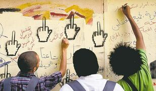 Youth activists write on a wall in Tahrir Square, Cairo, earlier this week.