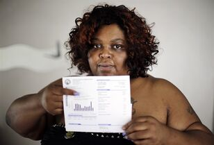 Nicole Hill holds up her past due water bill at her home in Detroit on June 25, 2014. THE CANADIAN PRESS/AP, Paul Sancya