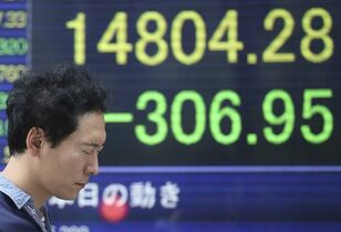 A man walks by an electronic stock board of a securities firm in Tokyo, Tuesday, Oct. 21, 2014. Asian stock markets drifted lower Tuesday after China reported its weakest economic growth in five years while Japan's benchmark dropped as investors cashed in gains from a 4 percent surge the previous day. (AP Photo/Koji Sasahara)