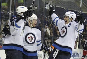 Winnipeg Jets' Bryan Little, center, celebrates his goal against the Columbus Blue Jackets with teammates Andrew Ladd, left, and Blake Wheeler during the first period of an NHL hockey game Tuesday, Nov. 25, 2014, in Columbus, Ohio. The Jets beat the Blue Jackets 4-2. (AP Photo/Jay LaPrete)