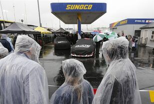 Fans watch as rain falls on Sprint Cup cars waiting for inspection at Richmond International Raceway in Richmond, Va., Saturday, April 25, 2015. The Sprint Cup Series auto race is scheduled for Saturday night, but the weather reports are calling for rain all evening. (AP Photo/Steve Helber)