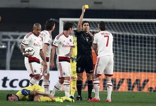 Referee Gianpaolo Calvarese, second from right, shows a yellow card to AC Milan's Jeremy Menez, right, during a Serie A soccer match between Chievo and AC Milan at Bentegodi stadium in Verona, Italy, Saturday, Feb. 28, 2015. (AP Photo/Felice Calabro')