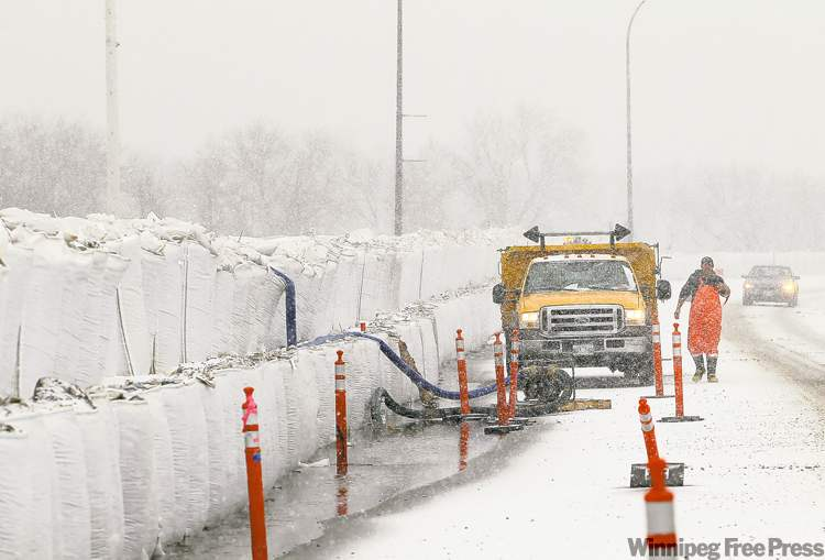Workers in Brandon pump water seeping under a sandbag dike back over the dike into Dinsdale Park as snow falls on Saturday.