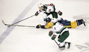 Nashville Predators center Filip Forsberg (9), of Sweden, dives as he chases the puck with Minnesota Wild center Mikael Granlund (64), of Finland, and Zach Parise (11) in the first period of an NHL hockey game Thursday, Feb. 26, 2015, in Nashville, Tenn. (AP Photo/Mark Humphrey)