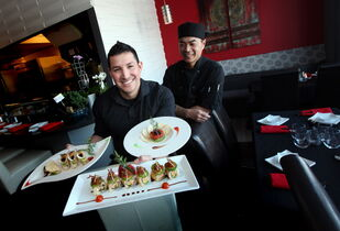 'Famous Amos' shows off some of the dishes served by Fusian Experience, including tacos made with wonton strips (far left). Partner and chef Chris Taing looks on to ensure Ramon commits no errors.