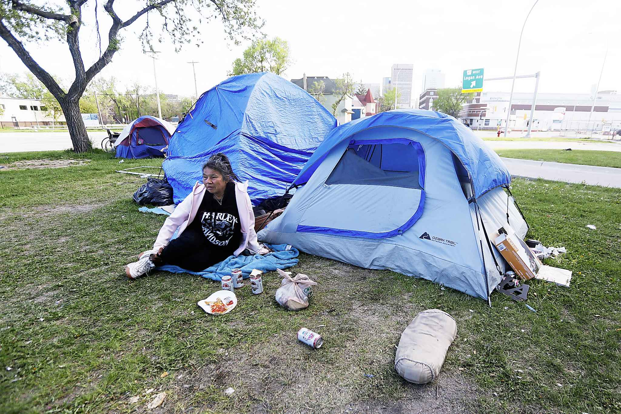 A resident of the Henry Avenue camp, Twilla, sits beside their tent in downtown Winnipeg.