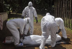 In this photo taken on Monday, Oct. 20, 2014, health workers carry the body of a woman suspected of contracting the Ebola virus in Bomi county situated on the outskirts of Monrovia, Liberia. Dozens of people quarantined for Ebola monitoring in western Liberia are threatening to break out of an isolation center in western Liberia because they have no food, the West African nation's state radio reported Thursday, Oct. 23, 2014. (AP Photo/Abbas Dulleh)