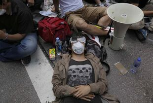 A protester takes a rest at a main street in Mong Kok district, Hong Kong Friday. Riot police cleared an offshoot Hong Kong pro-democracy protest zone in a dawn raid on Friday, taking down barricades, tents and canopies that have blocked key streets for more than two weeks, but leaving the city's main thoroughfare still in the hands of the activists.