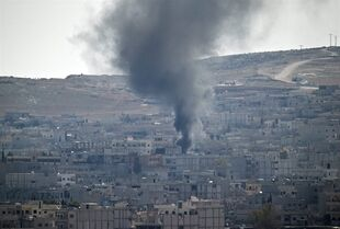 Smoke rises during fighting in Kobani, seen from a hilltop on the outskirts of Suruc, near the Turkey-Syria border, Friday, Oct. 24, 2014. Kobani, also known as Ayn Arab, and its surrounding areas, has been under assault by extremists of the Islamic State group since mid-September and is being defended by Kurdish fighters. (AP Photo/Vadim Ghirda)