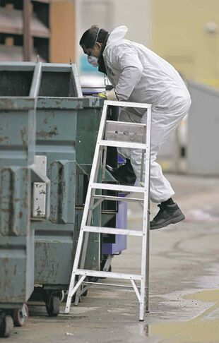 Winnipeg police search for evidence in  a downtown trash container in February 2012.