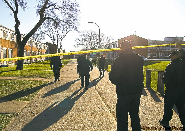 Police investigate the site of the first of the three shootings.