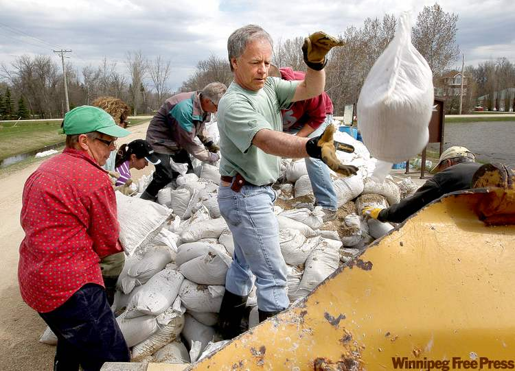 Ron Caron (centre) pitches some sandbags into a front-end loader on Ferry Road in the RM of Cartier Sunday afternoon as dike-building intensifies.
