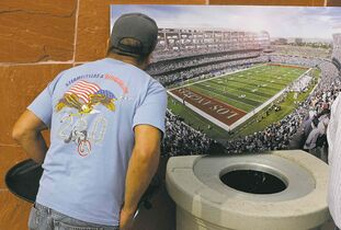 Damian Dovarganes / The Associated Press A keen fan checks out a rendering of the proposed stadium Friday.