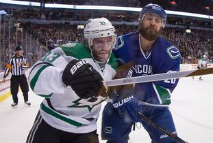 Vancouver Canucks' Dan Hamhuis, right, checks Dallas Stars' Alex Goligoski during the first period of an NHL hockey game in Vancouver, B.C., on December 17, 2014. Coming off a poor performance on Thursday in a loss to the Colorado Avalanche, the Vancouver Canucks will have to have a short memory when they continue their push for the playoffs on Saturday against the Dallas Stars. THE CANADIAN PRESS/Darryl Dyck