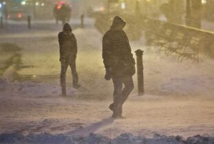 Pedestrians walk through wind-swept snow in downtown Brooklyn, Monday, Jan. 26, 2015, in New York. More than 35 million people along the northeast corridor rushed to get home and settle in Monday as a fearsome storm swirled in with the potential for hurricane-force winds and 1 to 3 feet of snow that could paralyze the Northeast for days. (AP Photo/Bebeto Matthews)